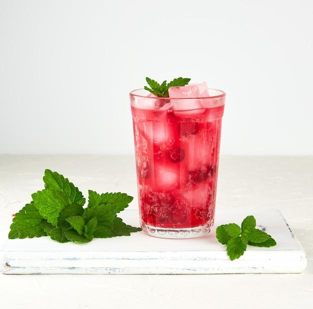 Estate bevanda rinfrescante con bacche di mirtilli e pezzi di ghiaccio in un bicchiere
