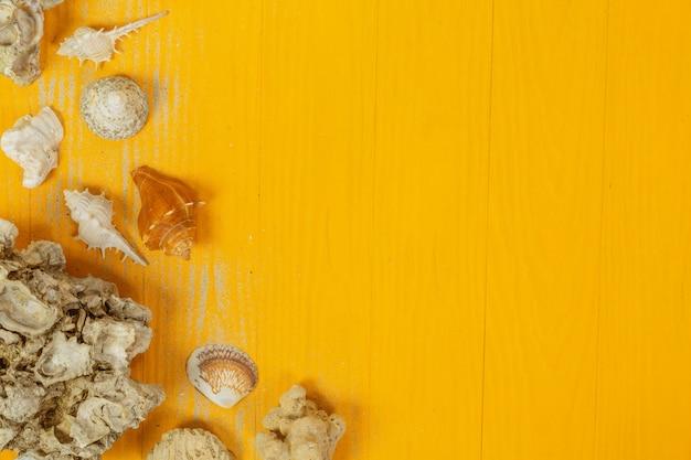 Estate con conchiglie, bicchieri, frutta e carta su un giallo