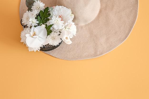 Estate con fiori bianchi freschi e un grande cappello di vimini, in tinta unita.