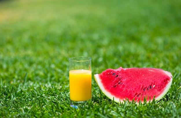 Estate e tema fresco: anguria rossa fetta matura e bicchiere di succo d'arancia su erba verde
