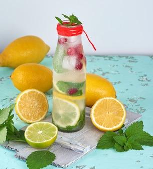Estate limonata bevanda rinfrescante con limoni, mirtillo, foglie di menta, lime in una bottiglia di vetro