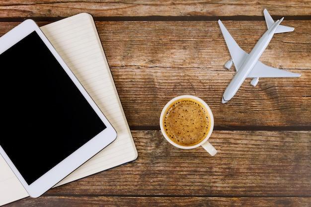 Estate per il concetto di viaggio sul concetto di viaggio di legno del fondo della tavola con l'utilizzo dell'aereo digitale del modello dell'aeroplano della compressa con le note della carta in bianco, tazza di caffè