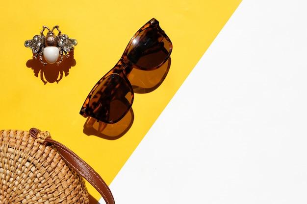 Estate piatta disteso scenario estivo, borsa, occhiali da sole e anello di moda su bianco e giallo
