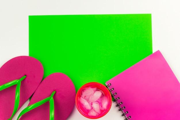 Estate piatta giaceva con infradito, notebook e bevanda fredda con ghiaccio