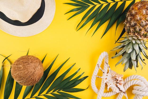 Estate piatta laici sullo sfondo. foglie di palma, cocco, ananas, occhiali da sole, corda, cappello di paglia e guscio su sfondo giallo.