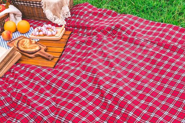 Estate picnic con un cesto di cibo sulla coperta nel parco. spazio libero per il testo