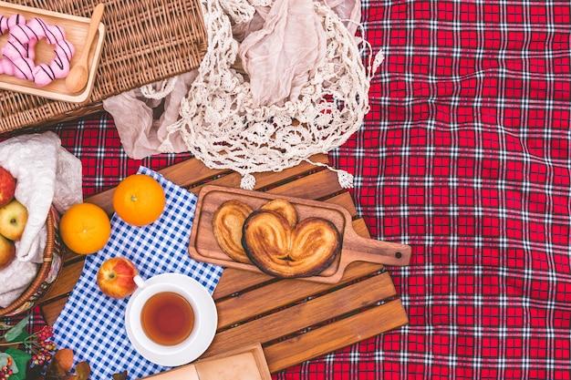 Estate picnic con un cesto di cibo sulla coperta nel parco.