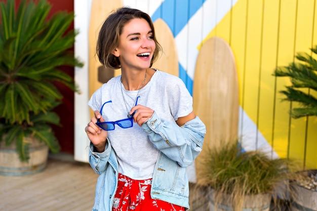 Estate primavera brillante positivo ritratto di donna bruna sorridente felice che indossa l'attrezzatura hipster femminile alla moda sorridente e divertirsi, in posa davanti a tavole da surf e palme.