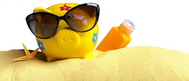 Estate salvadanaio con occhiali da sole sulla spiaggia
