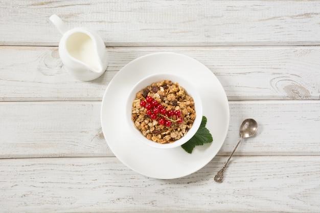 Estate sana colazione di muesli, muesli con latte brocca con decorazione di ribes rosso su tavola di legno. vista dall'alto.