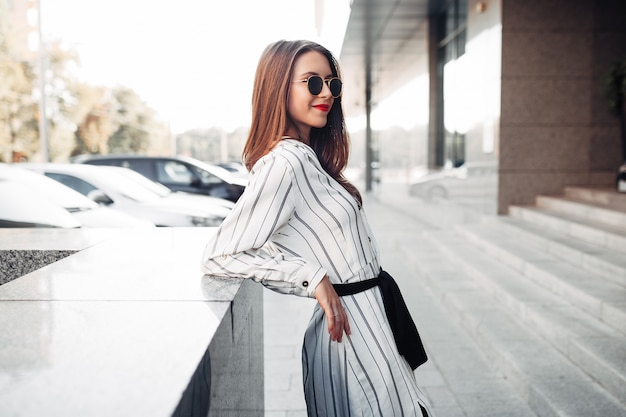 Estate soleggiata stile di vita ritratto di moda giovane donna elegante pantaloni a vita bassa