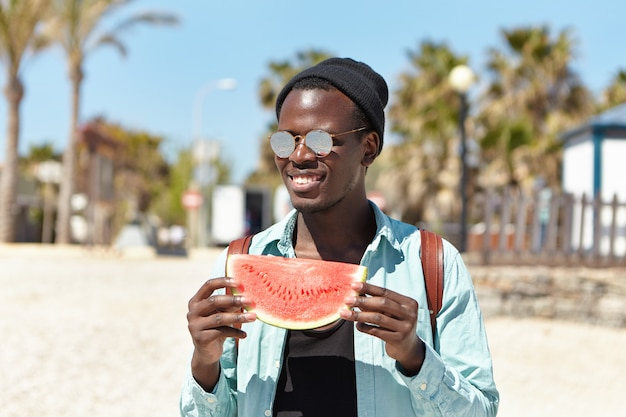 Estate, vacanze, vacanze e lifestyle. giovane viaggiatore maschio spensierato felice dalla pelle scura che ha piccolo picnic con gli amici dalla spiaggia, mangiando l'anguria deliziosa succosa