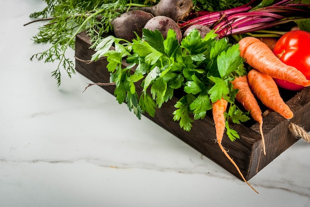 Estate, vendemmia autunnale. verdure biologiche fresche dell'azienda agricola in una scatola di legno sulle barbabietole di una tavola di marmo bianche, carote, prezzemolo, pomodori.