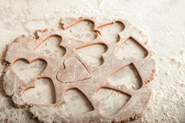 Estensione dell'impasto per il primo piano dei biscotti. pasta di pan di zenzero il 14 febbraio, farina, mattarello e copia spazio.