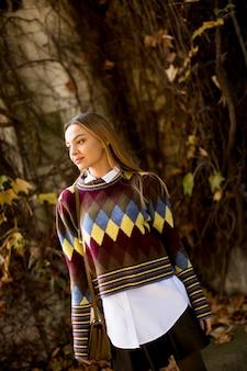 Esterno diritto della giovane donna al giorno soleggiato di autunno