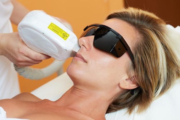 Estetista che rimuove capelli di giovane donna con il laser