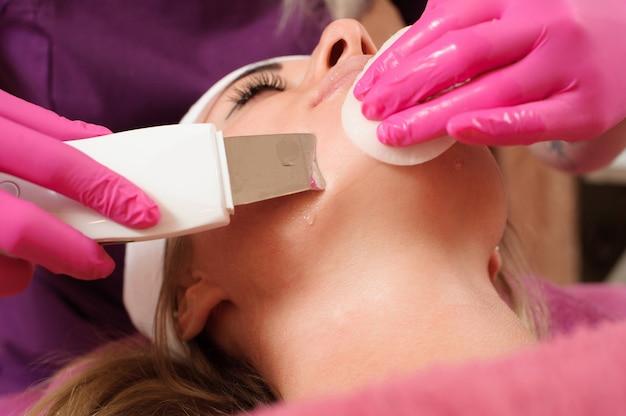 Estetista facendo una procedura di pulizia della pelle ad ultrasuoni