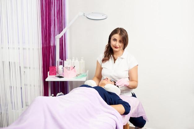 Estetista professionista sottoposto a procedura di estensione delle ciglia. master e cliente in un moderno salone di bellezza