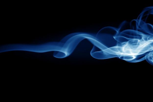 Estratto blu del fumo su fondo nero, concetto di oscurità