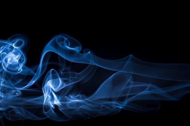 Estratto blu del fumo sul nero, concetto di oscurità