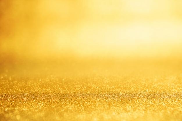 Estratto del fondo del nuovo anno dell'oro, luci d'annata del bokeh di scintillio giallo, defocused.
