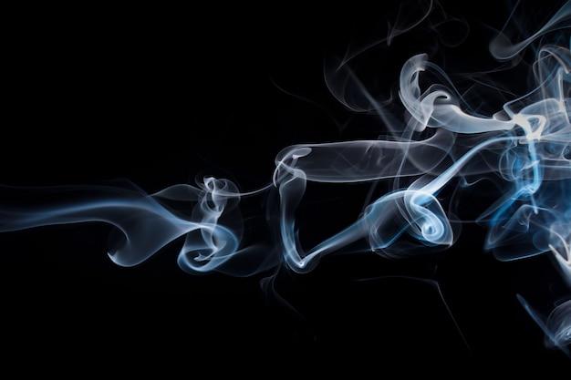 Estratto del fumo del gas su fondo nero. progettazione del fuoco