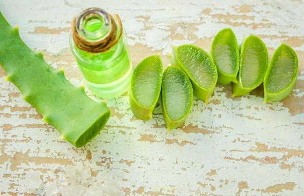 Estratto di aloe vera in una piccola bottiglia e pezzi sul tavolo. messa a fuoco selettiva