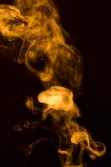 Estratto di fumi di fumo trasparente giallo su sfondo nero