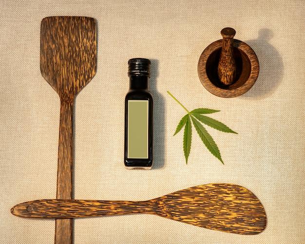Estratto di olio di canapa medicinale circondato da cucchiai di legno e un mortaio con un pestello.