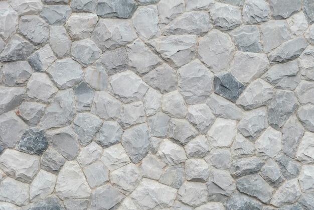 Estratto di superficie del primo piano alla vecchia parete di pietra nei precedenti strutturati del giardino