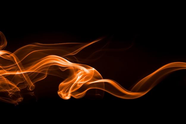 Estratto giallo del fumo su fondo nero, fuoco
