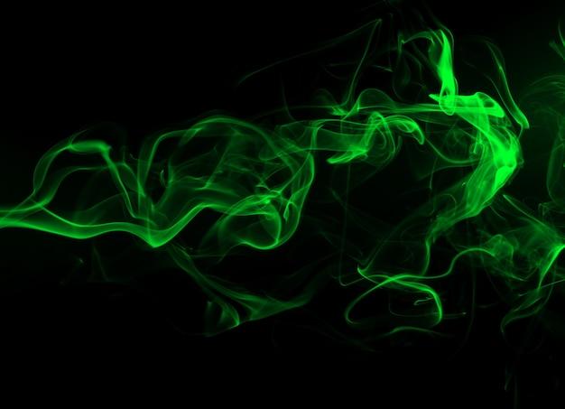 Estratto verde del fumo su fondo nero e sul concetto di oscurità
