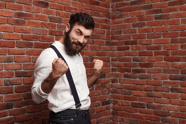 Esultanza del giovane uomo bello che posa sul muro di mattoni.