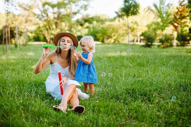 Età madre con una figlia piccola sdraiato sul prato nel parco e soffiando bolle di sapone. estate, ferie, congedo di maternità, infanzia