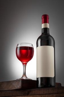 Etichetta beige in bianco sulla bottiglia di vino rosso e del bicchiere di vino sulla tavola di legno.