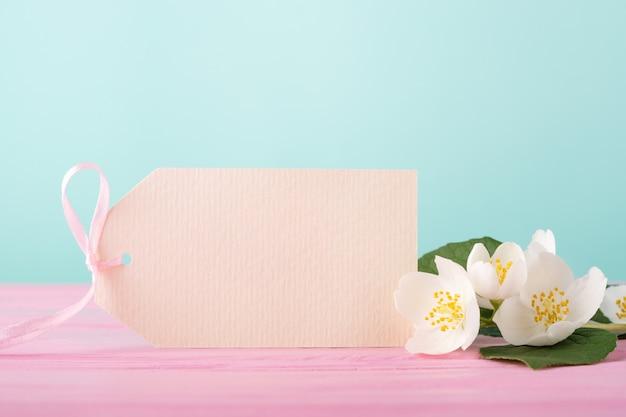 Etichetta bianca e fiori di gelsomino su rosa pastello e blu.
