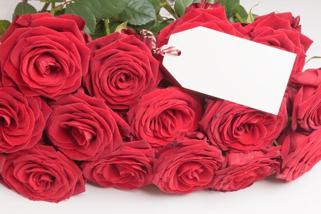 Etichetta bianca vuota con rose rosse su sfondo bianco. concetto di san valentino