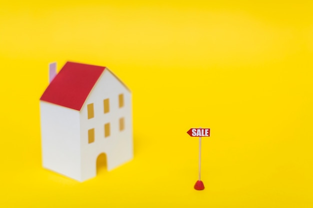 Etichetta di vendita davanti al modello della casa della sfuocatura contro il contesto giallo