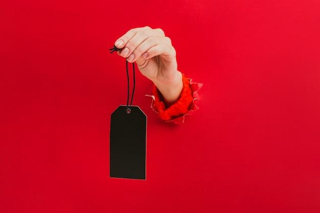 Etichetta nera in bianco in mano femminile attraverso un foro nel rosso. cartellino del prezzo, etichetta regalo, etichetta indirizzo.