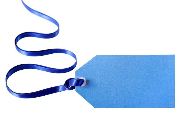 Etichetta regalo blu chiaro o biglietto di prezzo con nastro blu profondo isolato su bianco