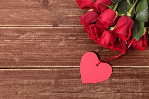 Etichetta regalo di san valentino e le rose sulla tavola di legno