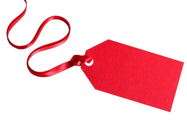 Etichetta rossa del regalo legata con il nastro rosso isolato