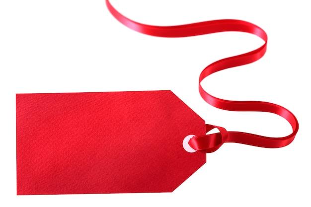 Etichetta rossa in bianco del regalo con il nastro riccio isolato su fondo bianco
