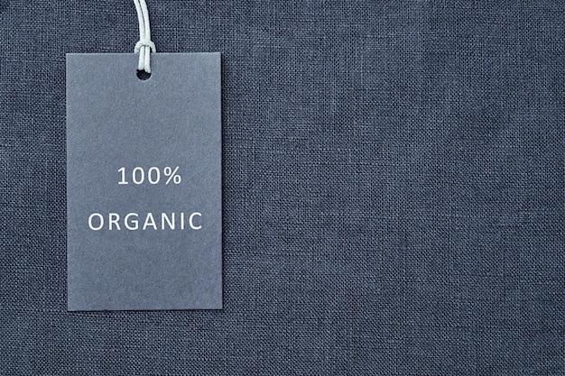 Etichetta su sfondo di tessuto di lino. 100% materiale organico