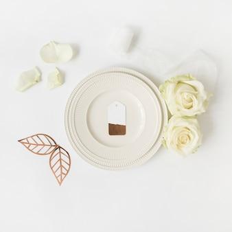 Etichetta vuota sul piatto bianco con rosa; foglie e nastro su sfondo bianco