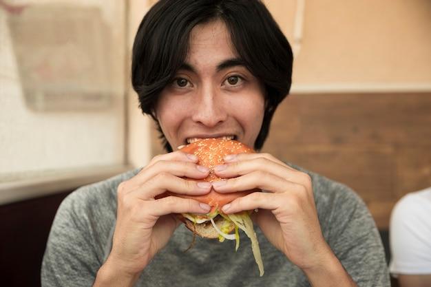 Etnico maschio mangiando hamburger e guardando la fotocamera