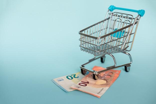 Euro banconote e carrello della spesa sul blu. concetto finanziario e di acquisto.