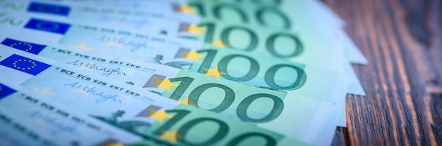 Euro banconote in contanti su un fondo di legno scuro.
