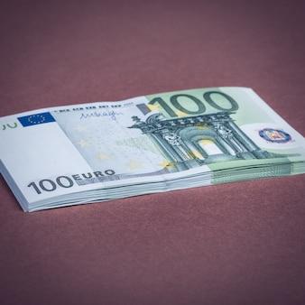 Euro in contanti su rosa e marrone.