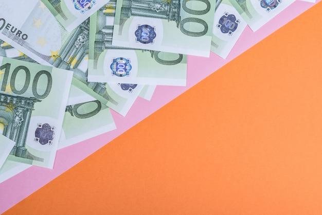 Euro in contanti su un rosa e arancio.